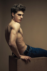 Beautiful (handsome) muscular male model in blue jeans sitting