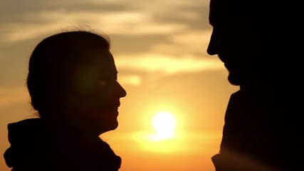 boy and girl kissing at sunrise(close-up)