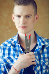 Young handsome man in blue casual shirt holding scissors