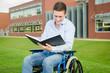 lächelnder Mann im Rollstuhl hält Notizbuch