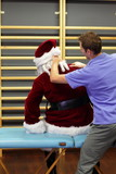 male therapist massaging stressed Santa Claus
