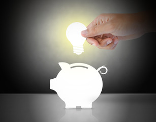 Male hand putting light bulb into a piggy bank, idea concept
