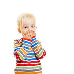 Kind hält sich den Mund zu