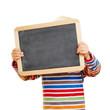 Kind hält leere Tafel vor das Gesicht