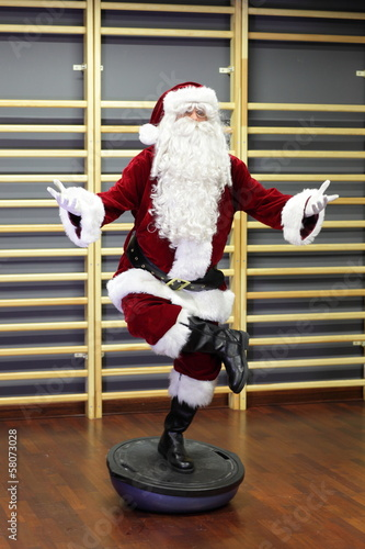 Santa Claus Fitness training on stablity hemisphere