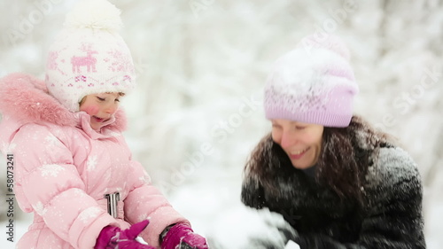 Happy woman and child playing with snow in winter. Slow motion
