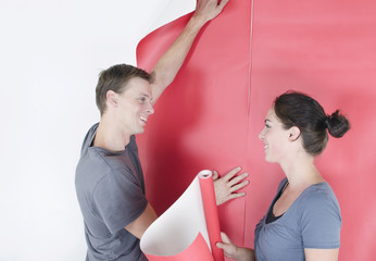 Happy couple wallpapering their home interior