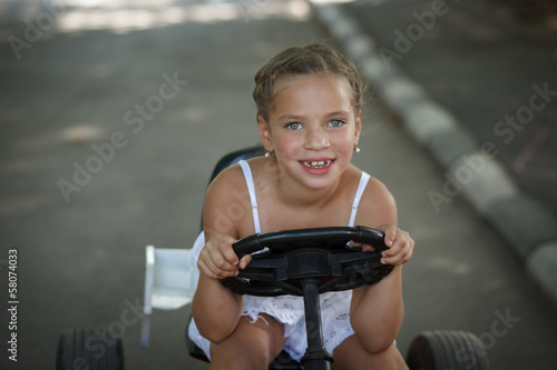 Driving little girl. Beautiful cheerful