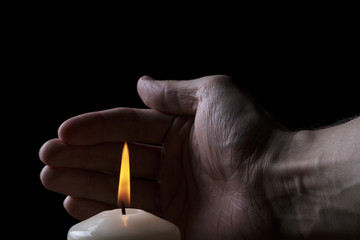adult male hand protect burning candle