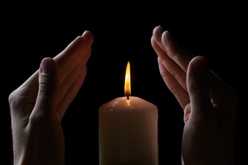 adult male hands protect burning candle