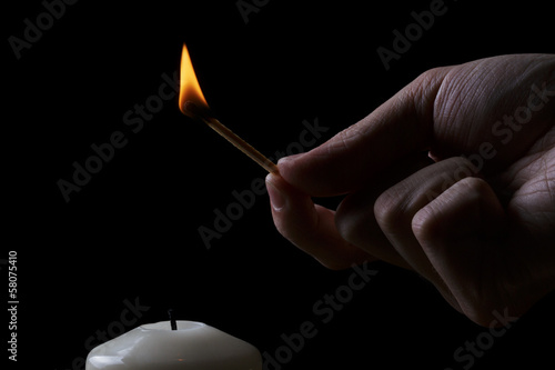 adult man hand set fire a candle