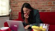 Businesswoman using laptop and sitting on the sofa in her flat