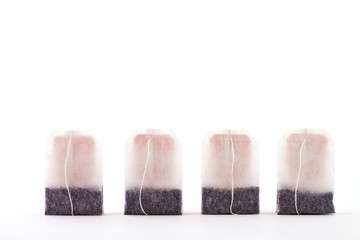 4 tea bags on white background
