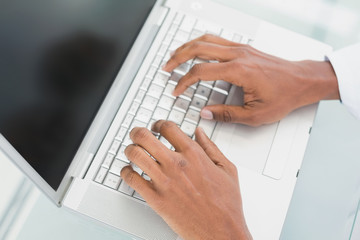 Hands using laptop at medical office