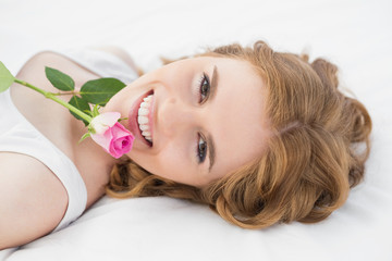 Pretty young woman resting in bed with rose