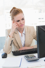Worried businesswoman looking at computer in office