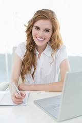 Smiling elegant businesswoman writing document at desk