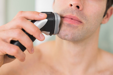 Extreme Close up of shirtless man shaving with electric razor
