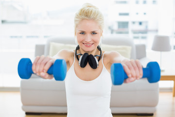 Smiling woman with dumbbells at fitness studio
