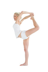 Sporty woman stretching body while balancing on one leg