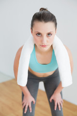 Tired woman with towel around neck at fitness studio