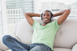 Relaxed young Afro man with headphones sitting on sofa