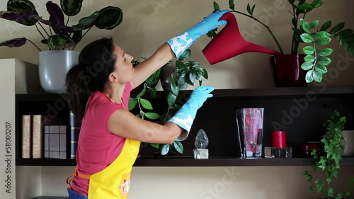 young woman watering flowers at home