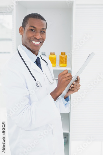 Smiling doctor writing a prescription in medical office