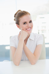Smiling businesswoman sitting at office desk