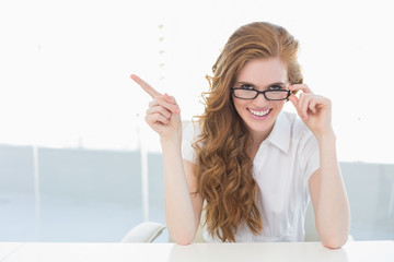 Cheerful businesswoman pointing to side in office