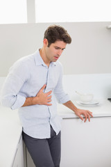 Casual man with stomach pain in the kitchen