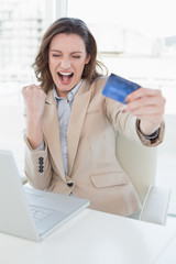 Excited businesswoman doing online shopping in office
