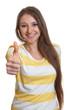 Junge Frau mit sehr langen Haaren zeigt Daumen hoch