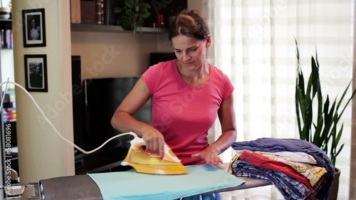 housekeeper ironing clothes on the board