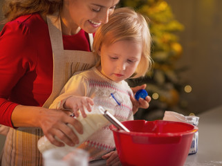 Mother and baby making christmas cookies in kitchen