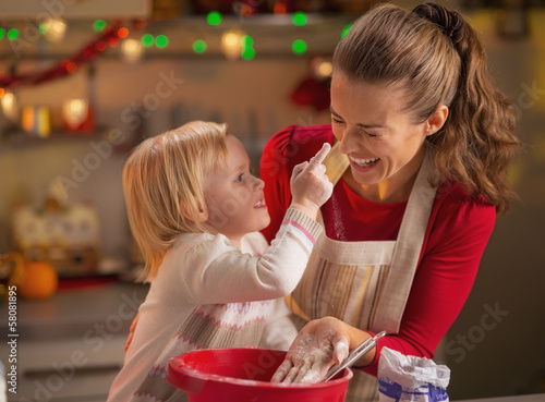 Baby trying to smear mothers nose with flour while making cookie