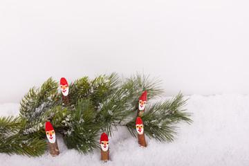 Tannenzweig mit Weihnachtsmännchen im Schnee