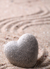 Grey zen stone in shape of heart, on sand background