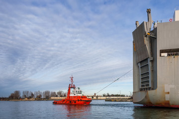 Tug boat helps to maneuver a large ship