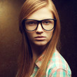 Young beautiful red-haired girl wearing trendy glasses