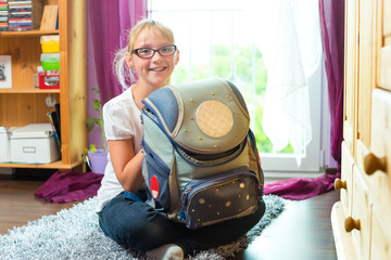 Girl with school bag in her room at home