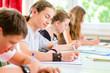 Schüler schreiben Klassenarbeit oder Test in Schule