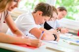 Fototapety Schüler schreiben Klassenarbeit oder Test in Schule