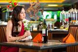 Chinese woman waiting in restaurant for date