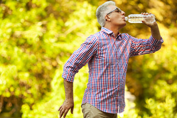 Healthy active life concept. Mature (old) man drinking water