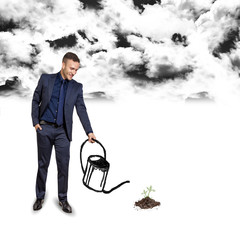 businessman growing below black clouds