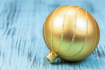 Christmas bauble over blue, rustic  wooden background