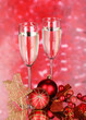 Glasses of champagne and Christmas balls on red background