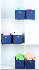 Blue textile boxes with towels in white shelves