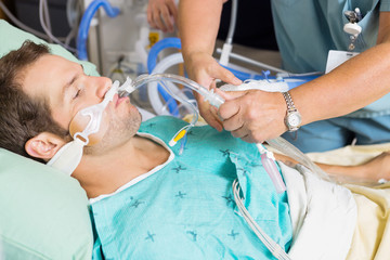 Nurse Adjusting Endotracheal Tube In Patient's Mouth